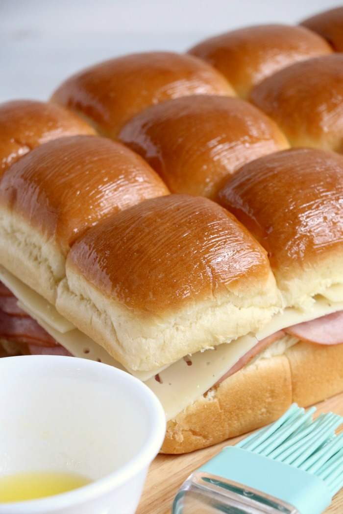 Ham and Cheese Sliders -Hawaiian rolls filled with ham, cheese, onions and a delicious mustard sauce, then brushed with butter. A great appetizer to feed a crowd!
