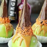 Witchy Caramel Apples - Crisp and tart Granny Smith apples covered with melted caramel and topped with a chocolate covered sugar cone garnished with some Halloween-themed sprinkles.