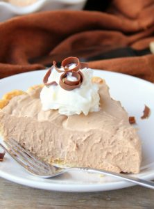 Mile High Chocolate Mousse Pie - Creamy, decadent chocolate mousse piled high and finished off with whipped cream and chocolate shavings.