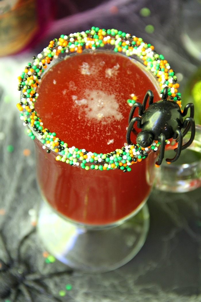 Spooky Halloween Punch - This Halloween punch is only three ingredients! When served in a nonpareil-rimmed glass, the color of the candy starts dripping eerily into the punch, creating fun black streaks and darkening the color of the drink!