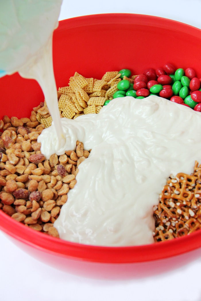 Easy Reindeer Chow - A delicious snack mix filled with pretzels, peanuts, Cheerios, Chex and M&Ms covered in white chocolate. Great for snacking and gift giving!
