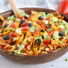 Dorito Taco Salad - This crunchy and zesty salad is made with seasoned ground beef, veggies, cheese and Doritos, then tossed with Catalina dressing. So delicious and serves a crowd!