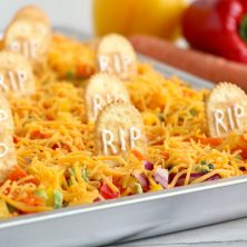 """Halloween Veggie Pizza - A spooky themed graveyard pizza featuring a flavorful ranch cream cheese covered crust, topped with colorful veggies and """"tombstone"""" crackers."""