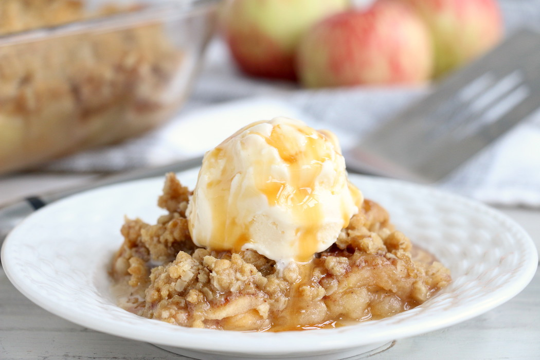 Easy Apple Crisp - A delicious, old-fashioned crisp made with sliced apples and a crunchy brown sugar oat topping. A scoop of vanilla ice cream and salted caramel sauce puts it over the top!