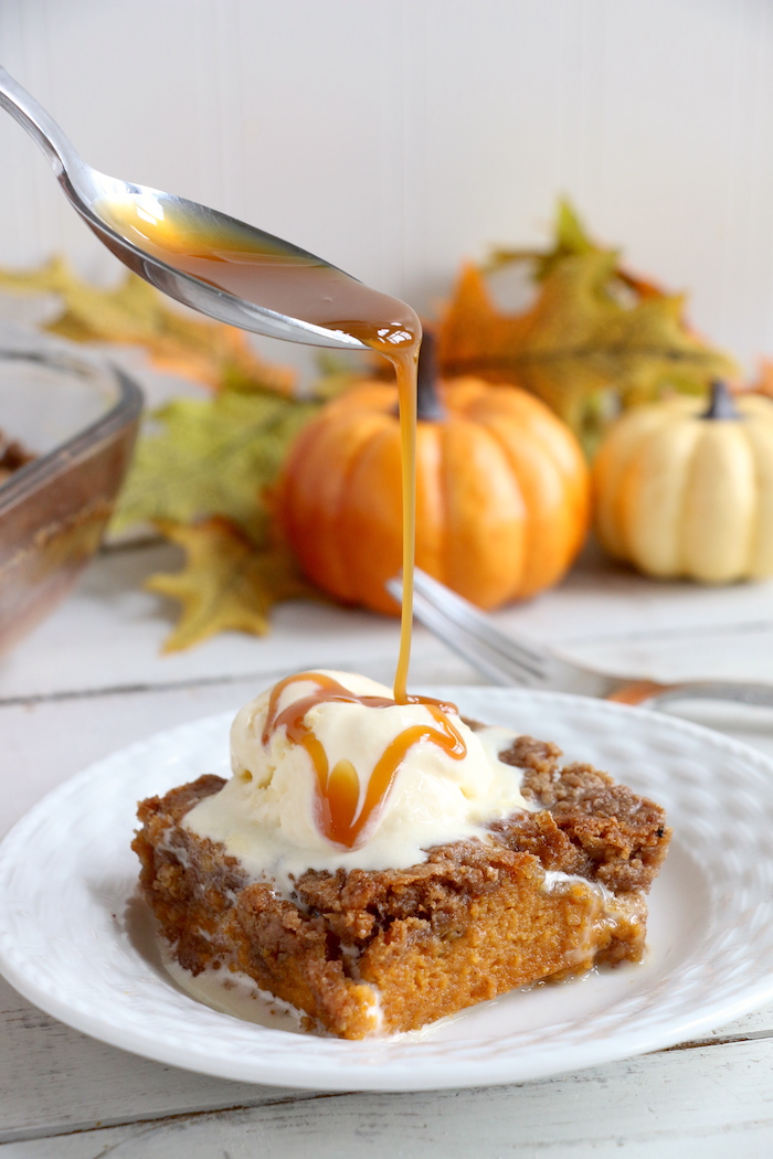 Pumpkin Dump Cake - An easy and delicious pumpkin spice cake topped with vanilla ice cream and caramel drizzle!