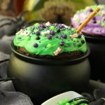 Witch Cauldron Mug Cake - A chocolate mug cake made in a ceramic witch cauldron with halloween-themed frosting and sprinkles!