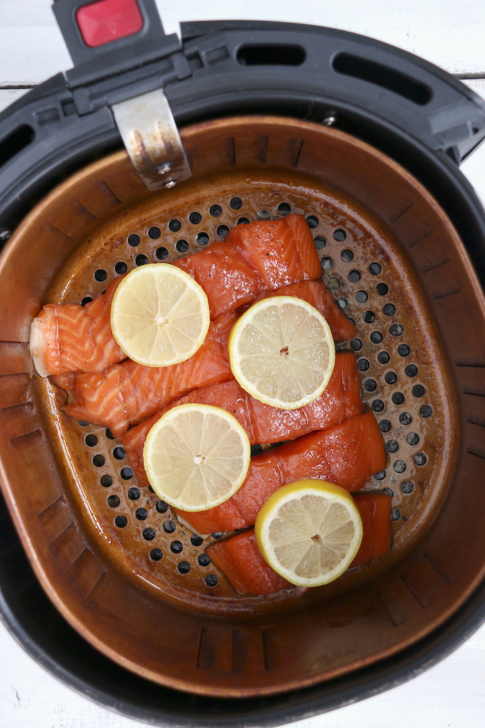 Salmon in an air fryer with lemon slices
