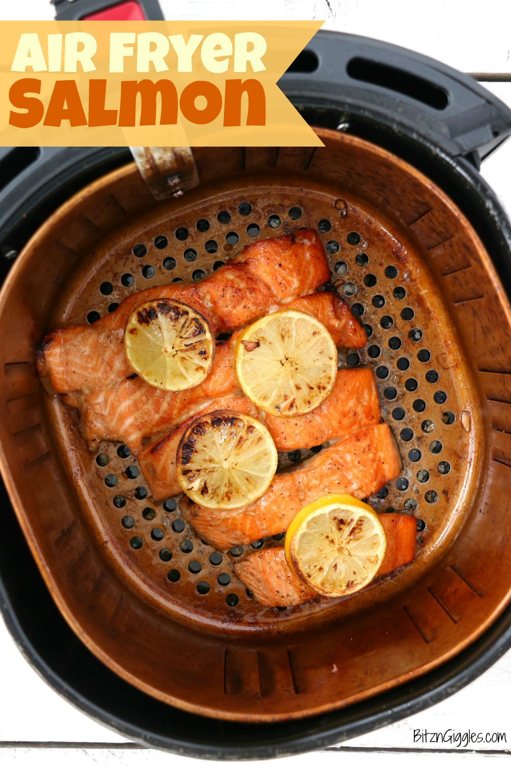 Salmon covered in lemon slices in air fryer basket