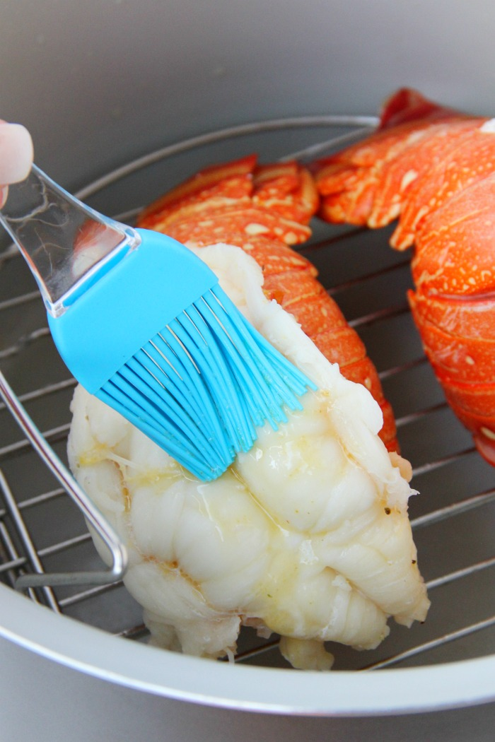 Brushing lobster tail with melted butter in Ninja Foodi