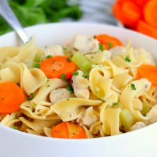chicken noodle soup in white bowl with spoon