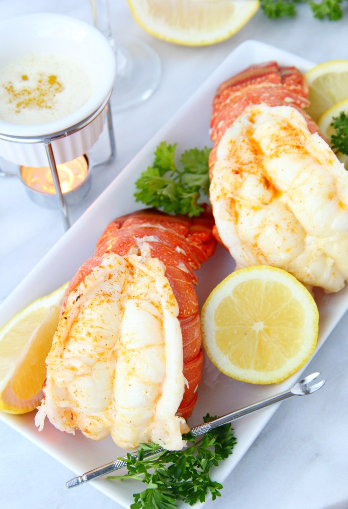 lobster tails on plate with lemon and melted butter on the side
