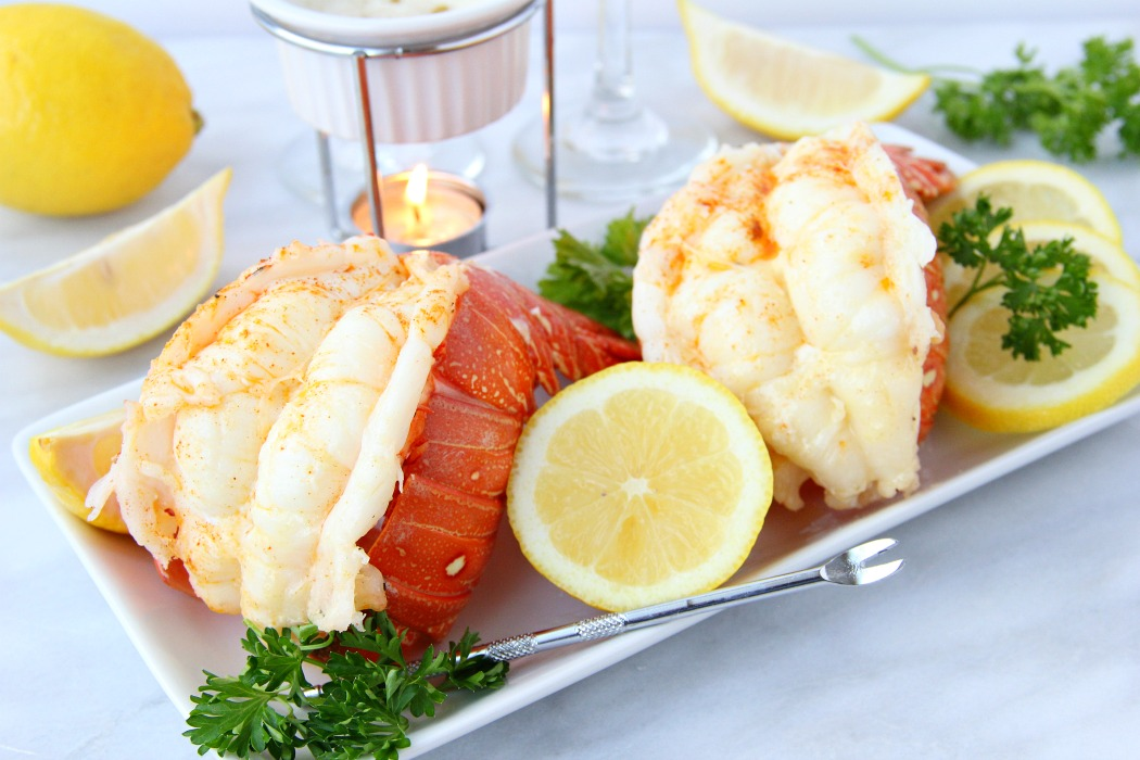 Lobster tails with lemon and melted butter in background