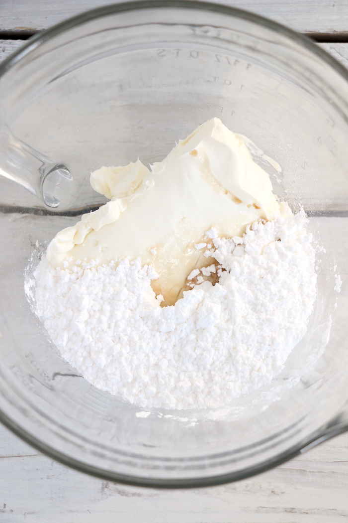 Glass bowl filled with cream cheese, powdered sugar and vanilla