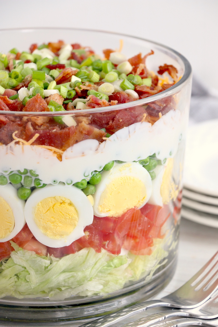 side shot of seven layer salad in trifle bowl