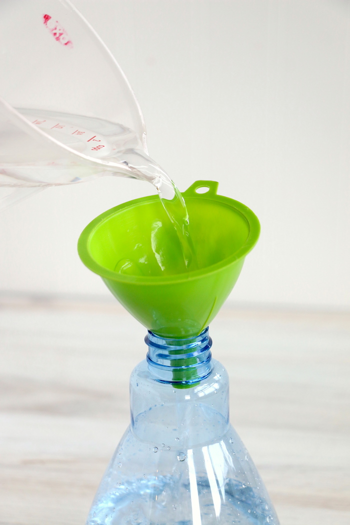pouring water from a measuring cup into a green funnel