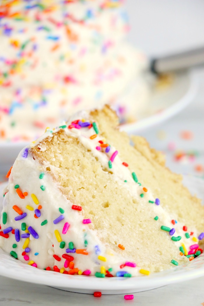 Piece of vanilla wacky cake with frosting and sprinkles