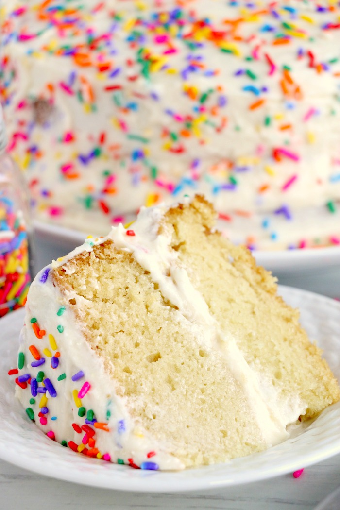 piece of layer cake with frosting and sprinkles