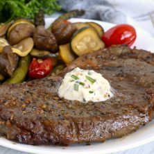 Steak with garlic butter and vegetables in the background