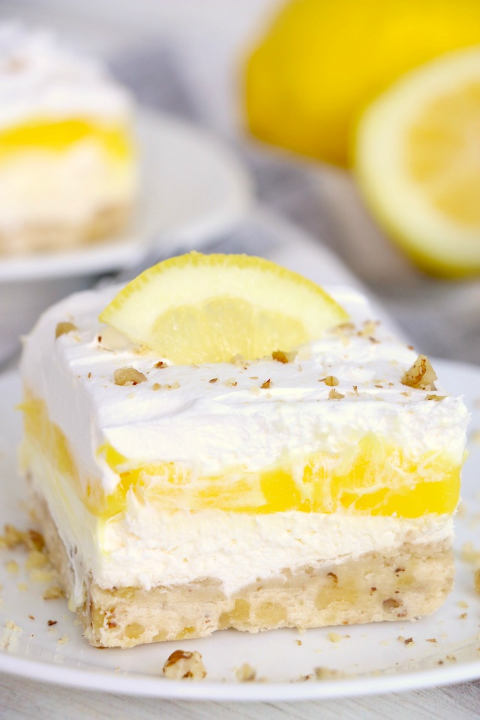 Piece of lemon lush dessert with lemon slice garnish