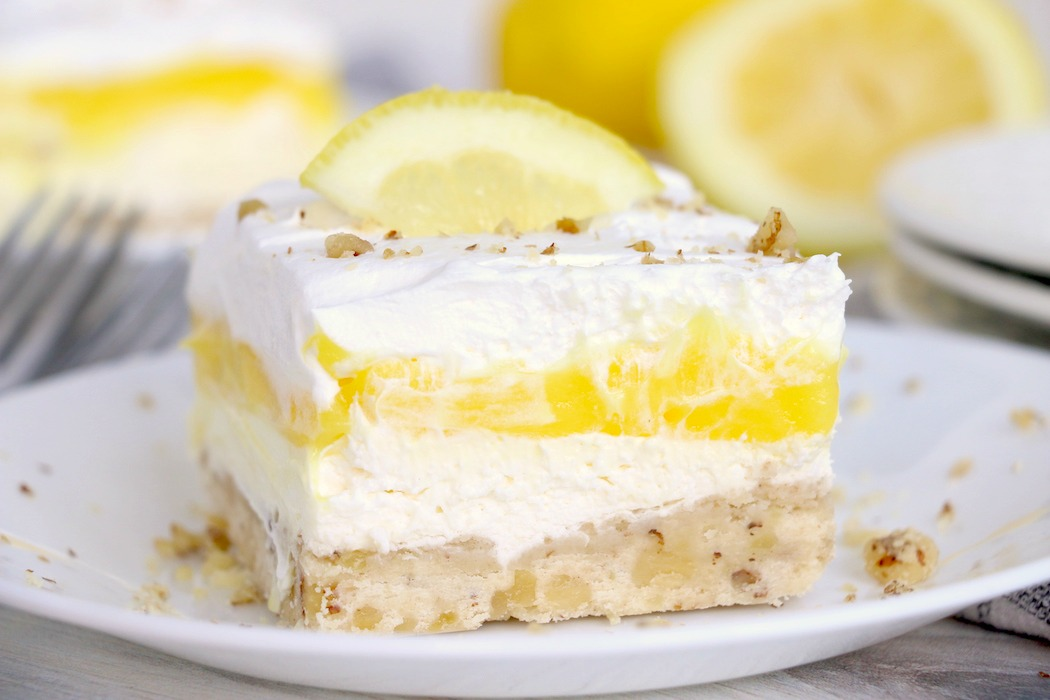 Lemon lush dessert on a plate with lemons in the background