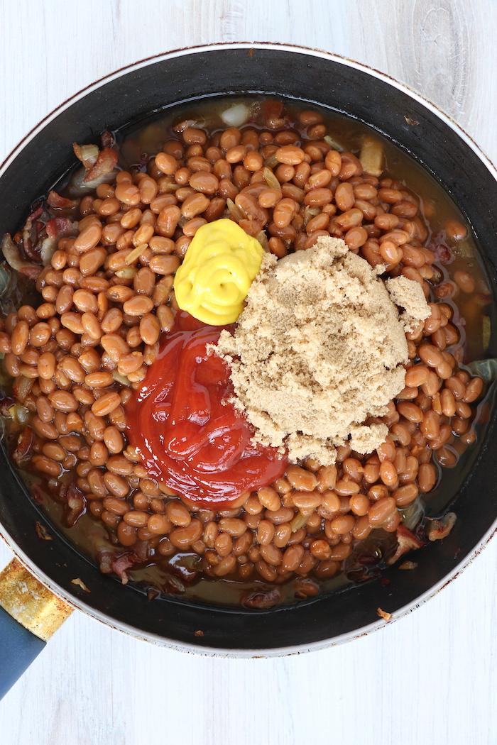 ketchup, mustard and brown sugar in pan of baked beans