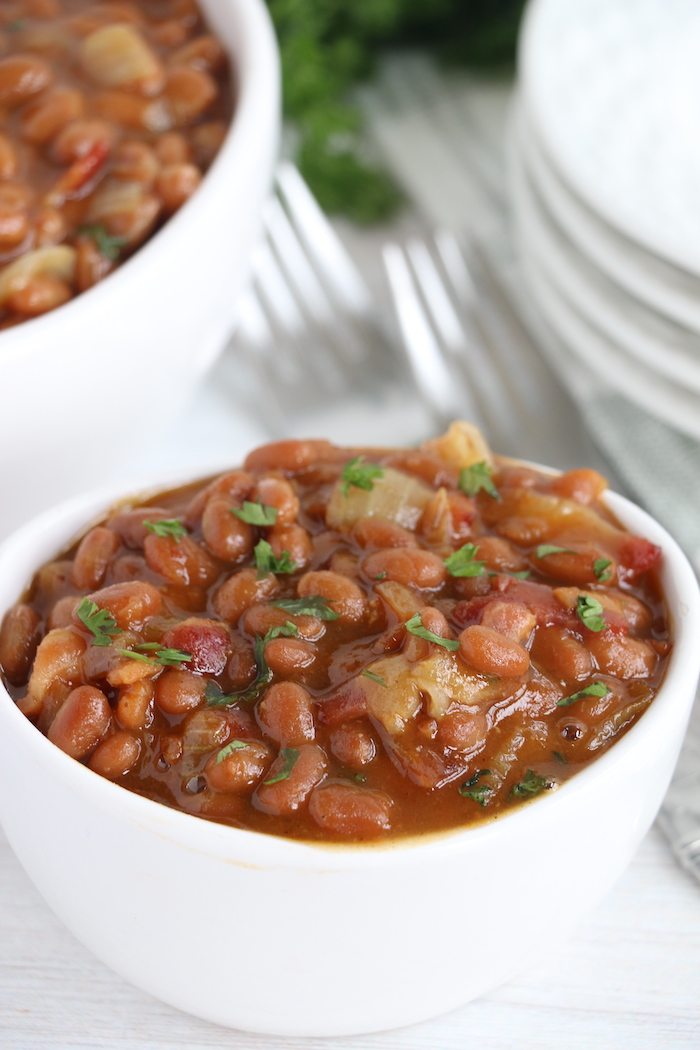 baked beans with fresh parsley in white bowl