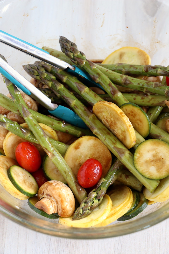 Mixing in marinade with an assortment of vegetables
