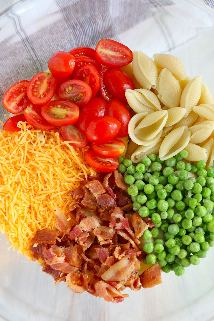 a bowl of pasta, bacon, peas, cheese and tomatoes