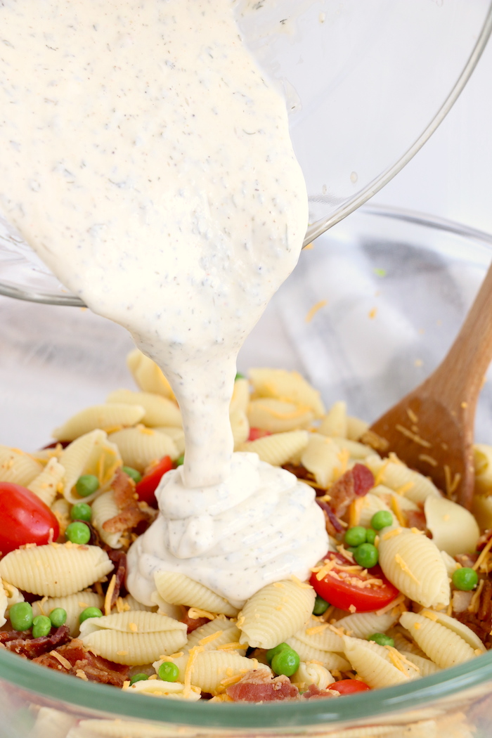 pouring ranch dressing over pasta salad