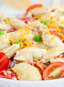 Pasta salad with peas, tomatoes, cheese and ranch dressing.