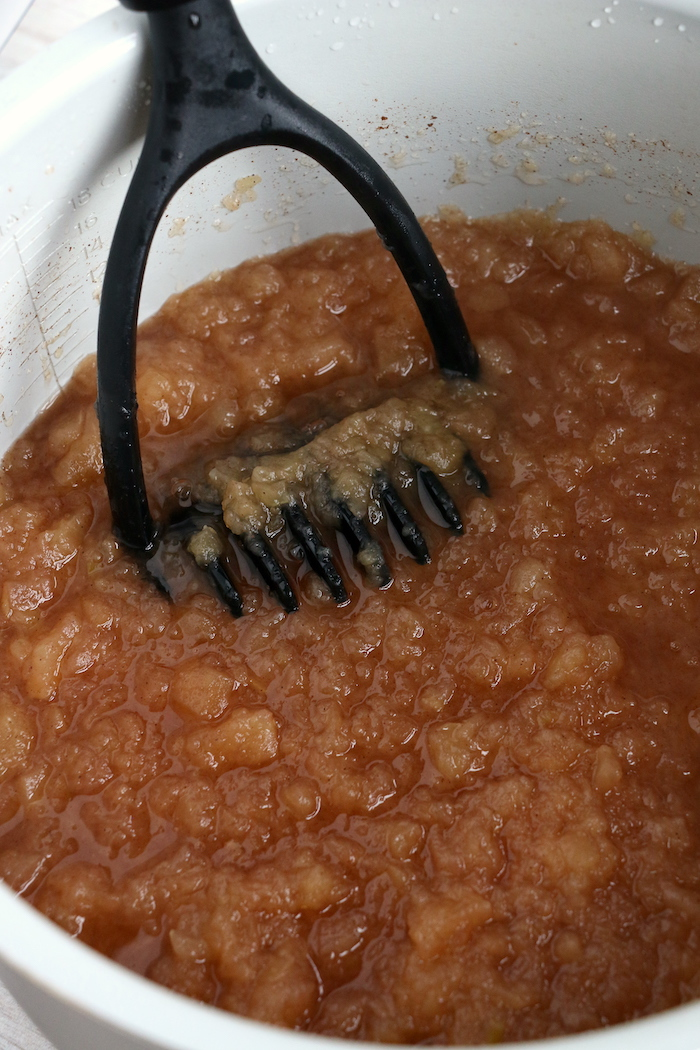 using a masher to mash apples in the Ninja Foodi cooking pot