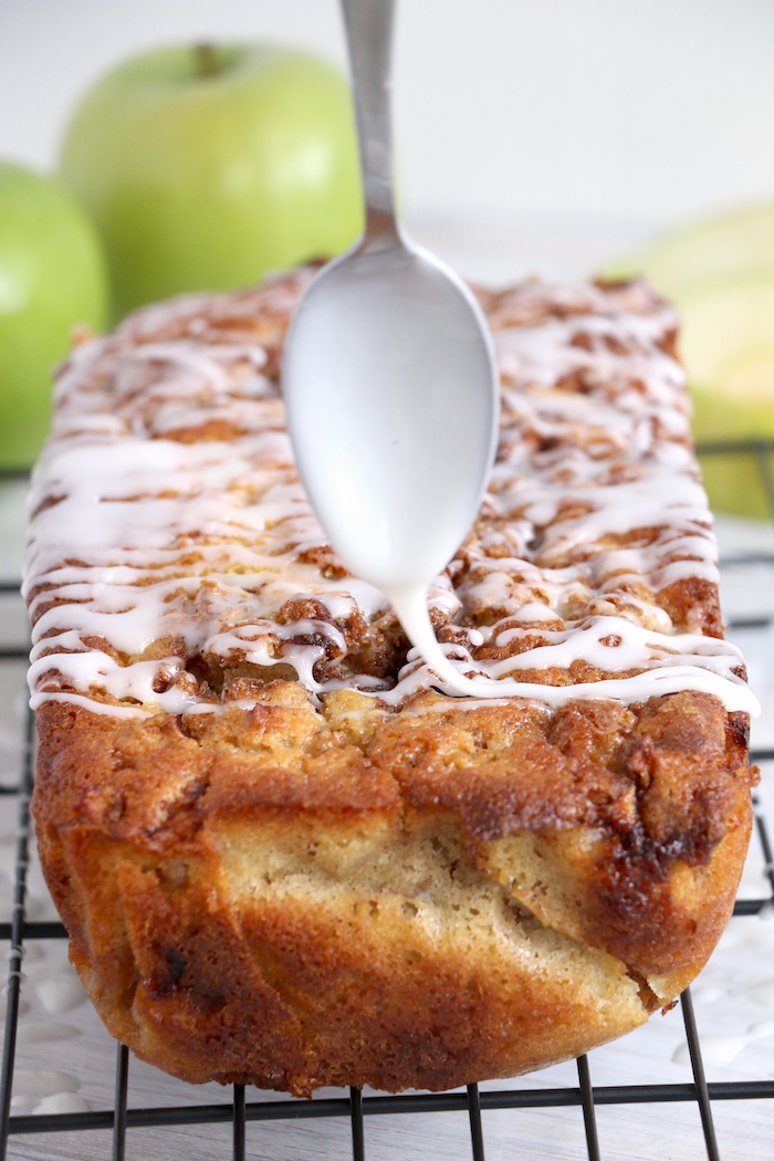 drizzling an apple bread loaf with icing