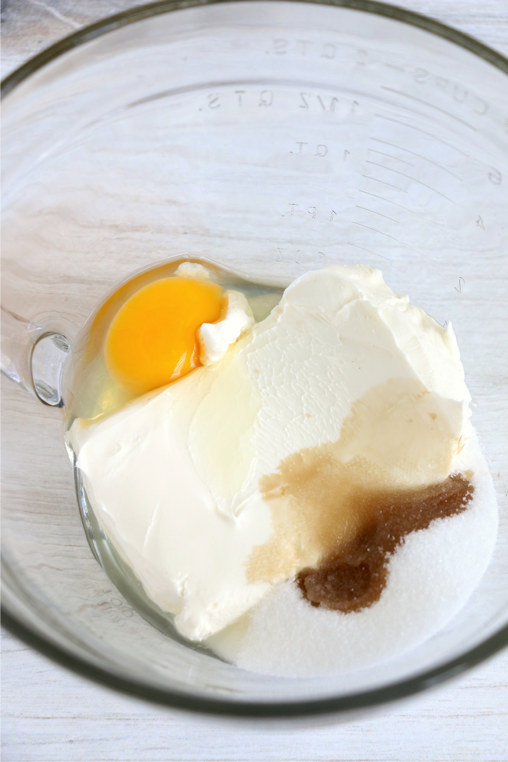 cream cheese, sugar, vanilla and an egg in a glass bowl