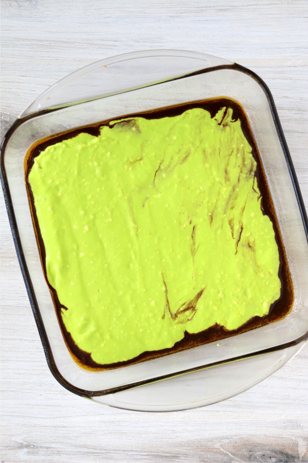 Neon green cream cheese layer on top of brownie layer in baking dish