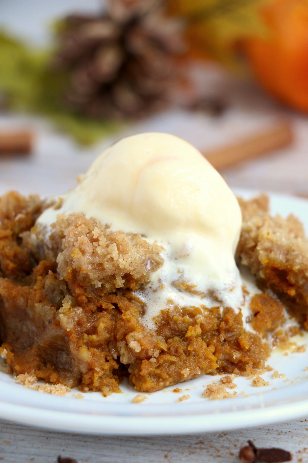 pumpkin crisp on a plate topped with a scoop of ice cream