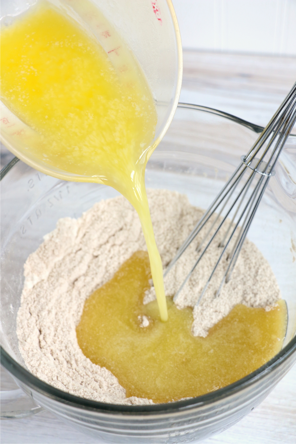 pouring melted butter into a flour mixture