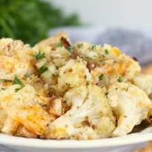 plate of cauliflower topped with cheese and parsley