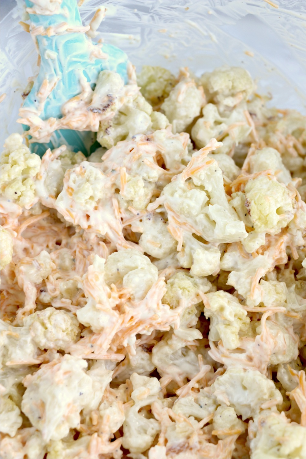 Mixing cauliflower florets with sour cream mixture