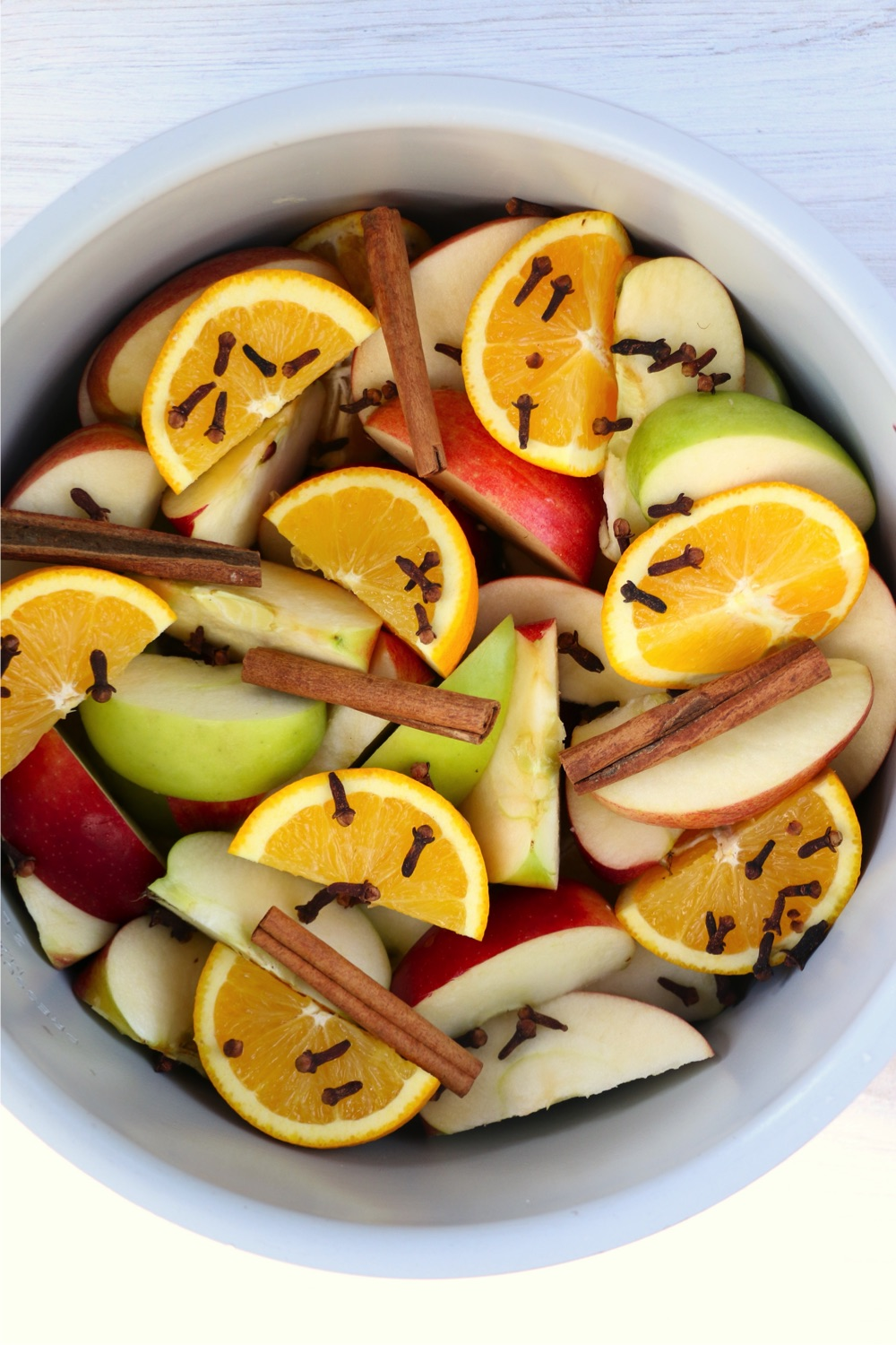 Ninja Foodi cooking pot filled with fresh fruit slices, cloves and cinnamon sticks