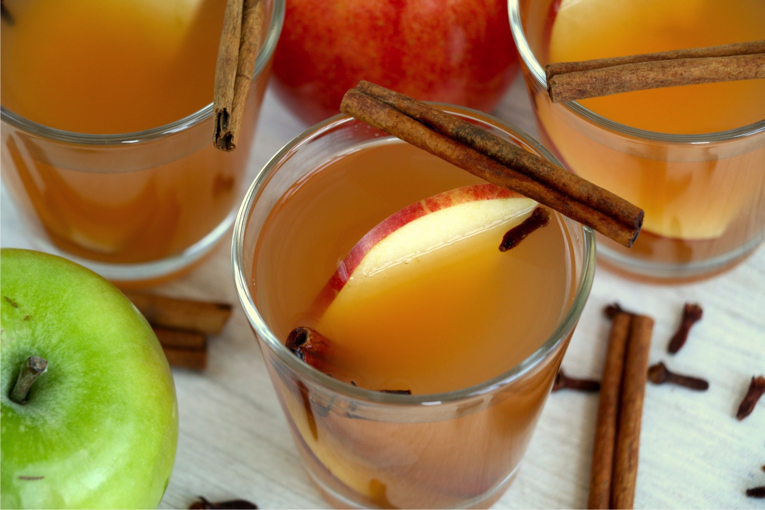 glass of apple cider garnished with apple slices and cinnamon sticks