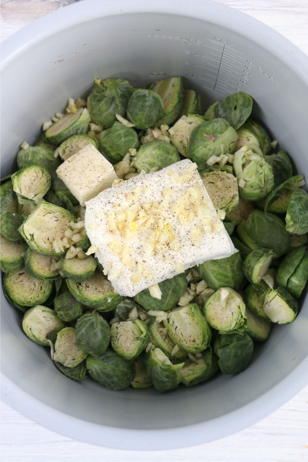 cream cheese, butter, garlic and seasonings on top of brussels sprouts in Instant Pot