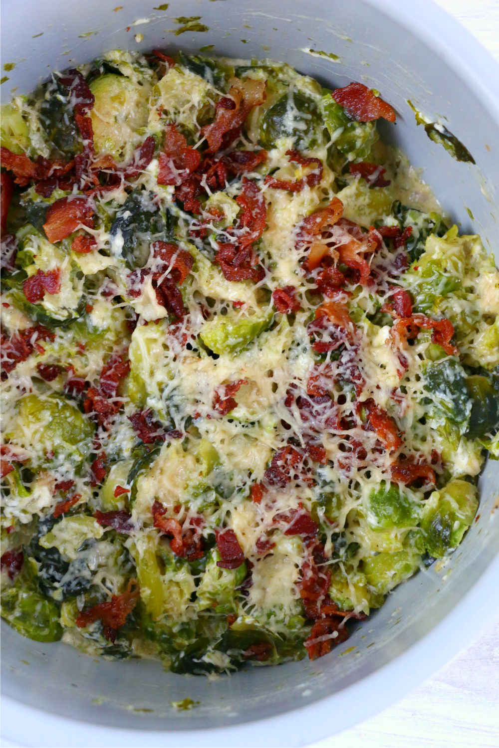 Melted parmesan cheese and bacon on top of Brussels Sprouts in Foodi cooking pot