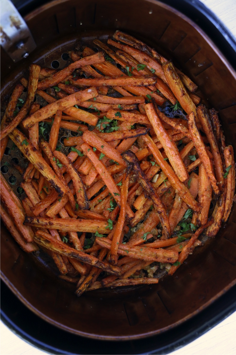 Cooked carrot fries in air fryer basket