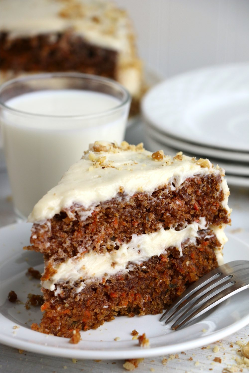 Piece of layered carrot cake on plate with glass of milk in background