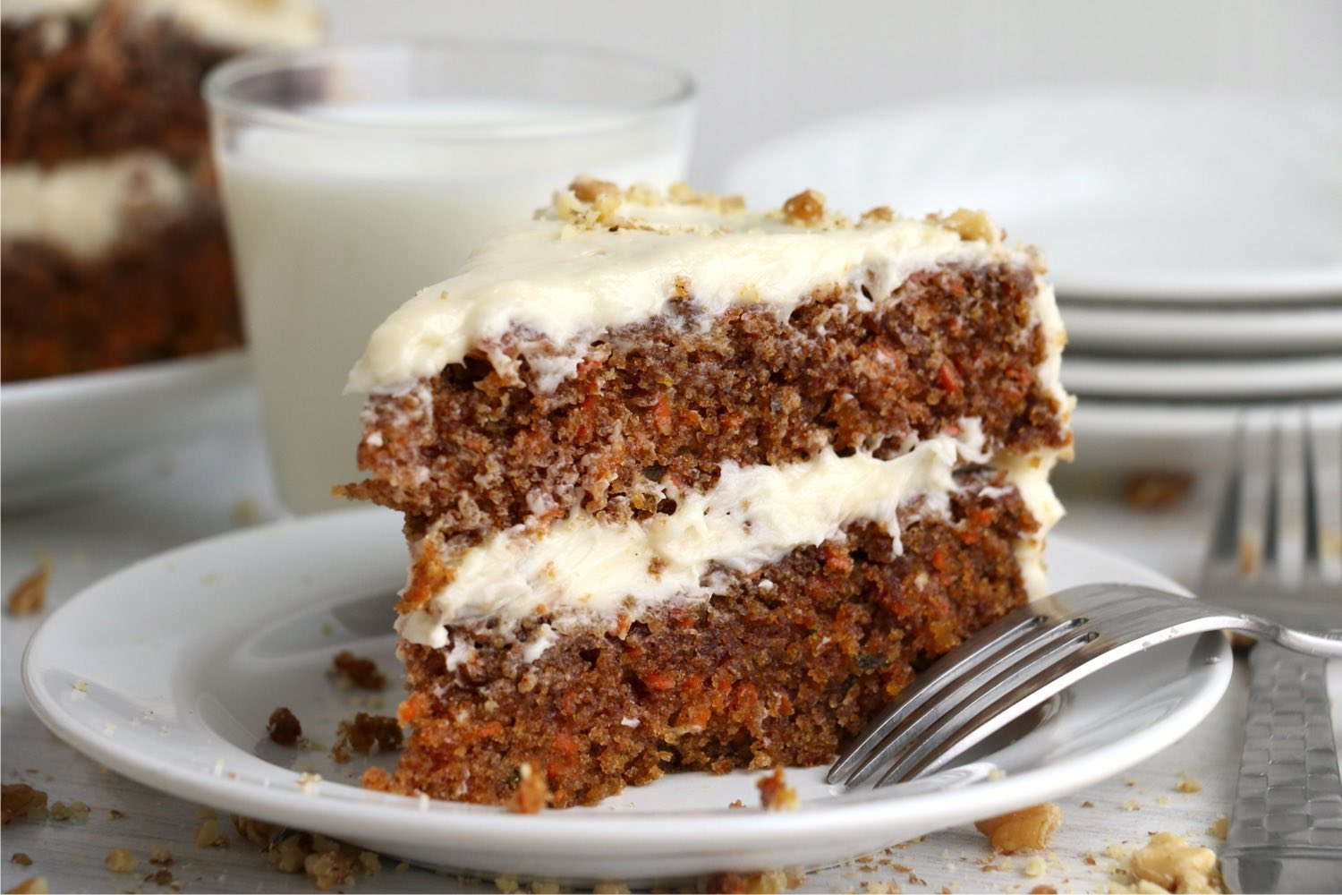 layered carrot cake on a plate with fork