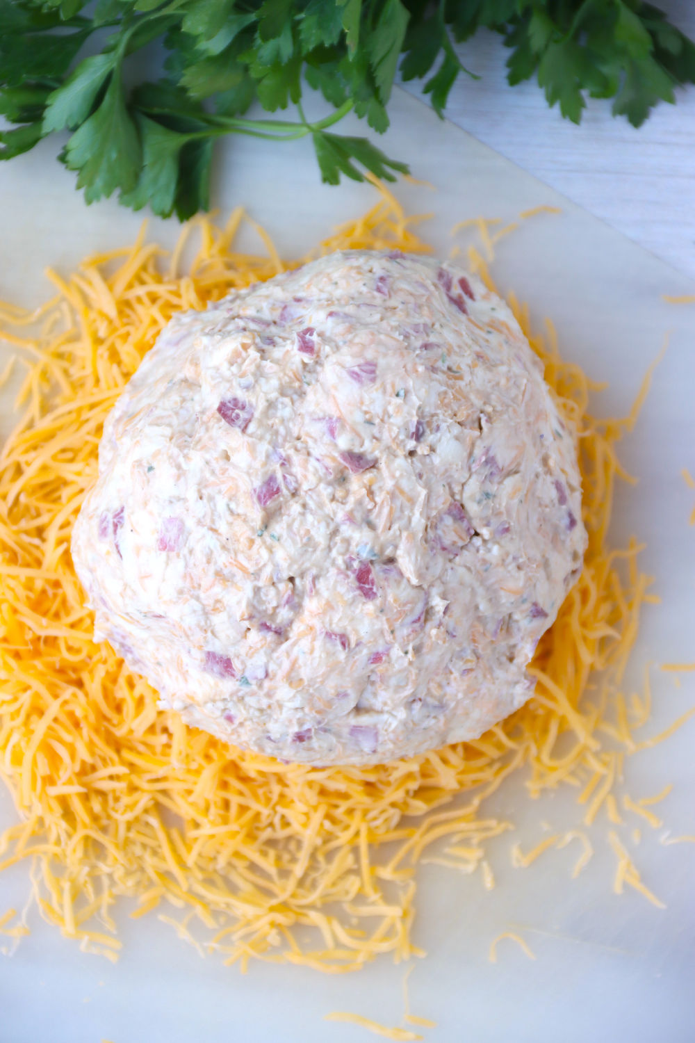 cheese ball sitting on top of pile of shredded cheese