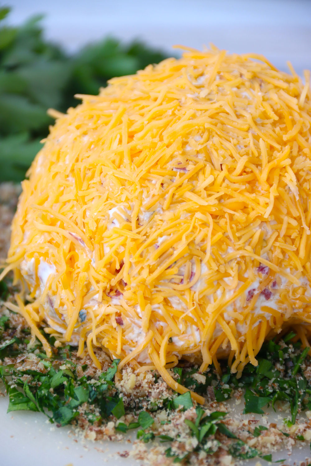 cheese ball covered in shredded cheese