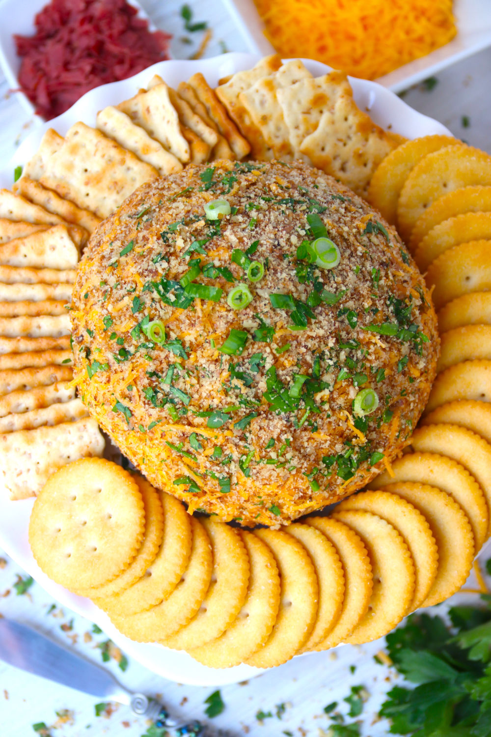 top shot of cheese ball covered with parsley and green onions