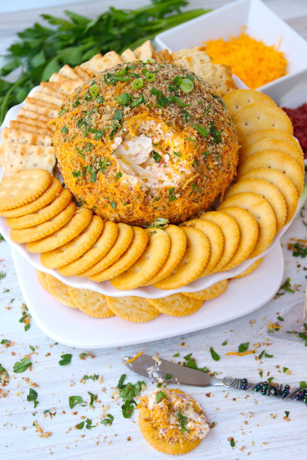 Cheese ball on a cake stand surrounded by crackers