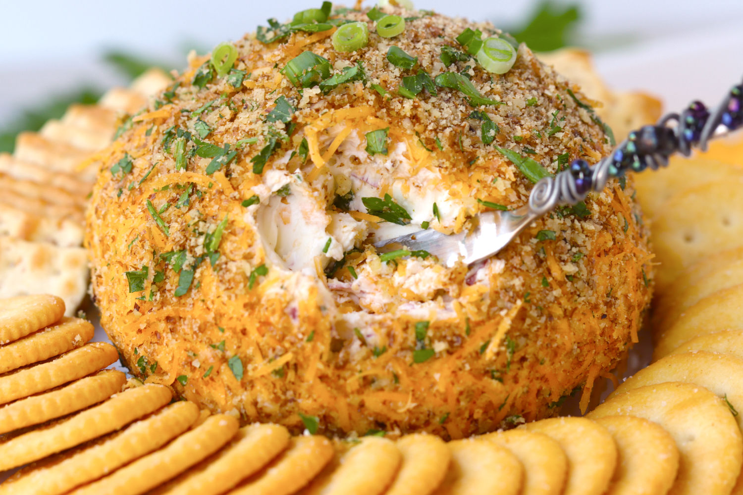 digging into cheese ball with a spreader knife